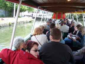 Group of people on a boat, on the canal, seen from inside boat at rear