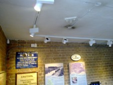 Track with lamps mounted on ceiling, display of notices lit on wall